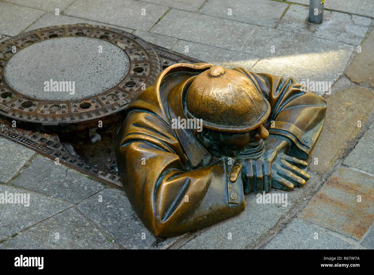 Kanaldeckel mit Skulptur Cumil, der Zuschauer von Victor Hulik, 1998, Bratislava, Slowakei Stockbild