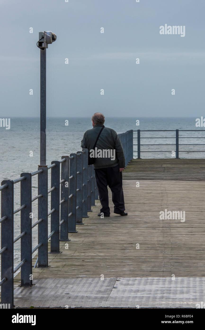 Ältere oder älteren Mann stand auf einem Pier am Meer Blick Meer auf einem grauen und bewölkten Tag. Stockbild
