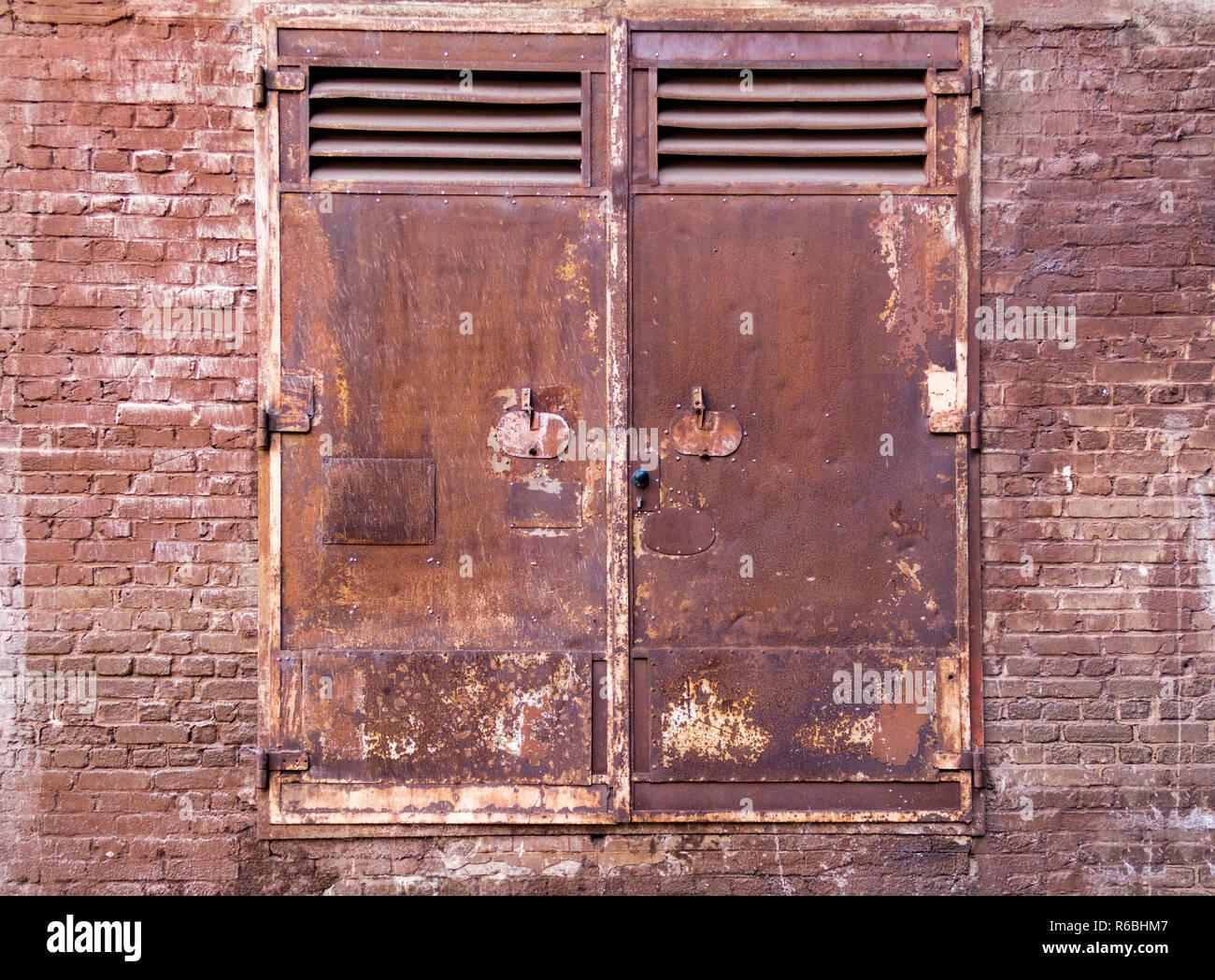 Verwitterte rusty industrielle Landschaft mit alten korrodierte metallic Türen und schmutzige Backsteinmauer Stockbild