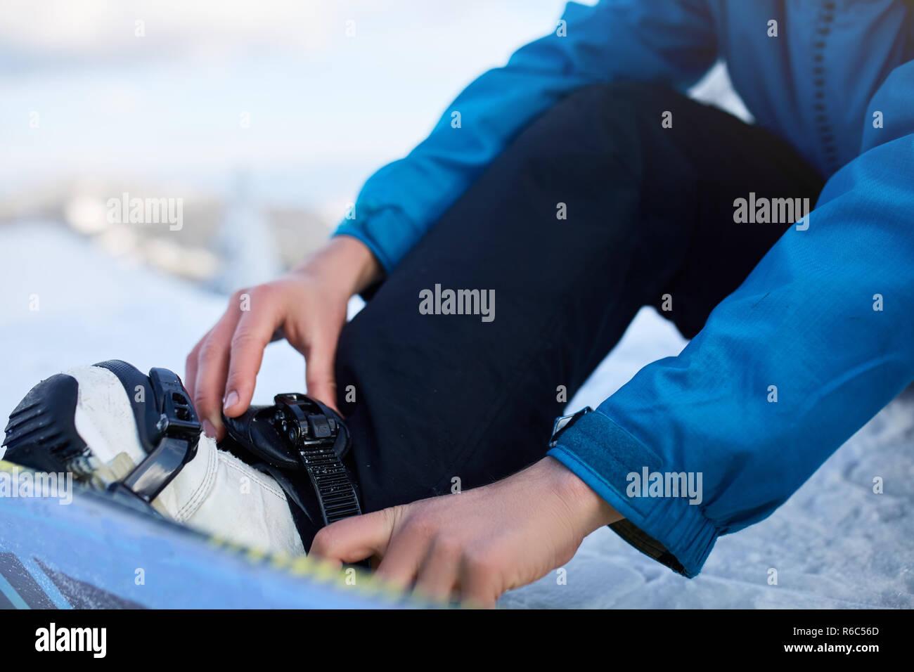 Snowboarder Bänder in seine Beine in Snowboardschuhe in modernen fast flow Bindungen mit Gurten. Reiter am Ski Resort bereitet sich für Freeride Session und. Mann, der modische Outfit. Füße close-up. Stockbild