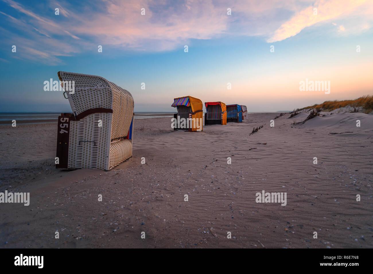 Strandkörbe im Sonnenuntergang unter blauem Himmel Stockfoto