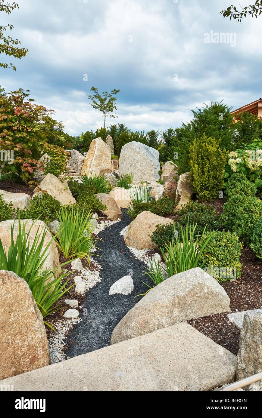 Ein Garten Mit Grossen Steinen Und Pflanzen Von Koniferen Am Hang