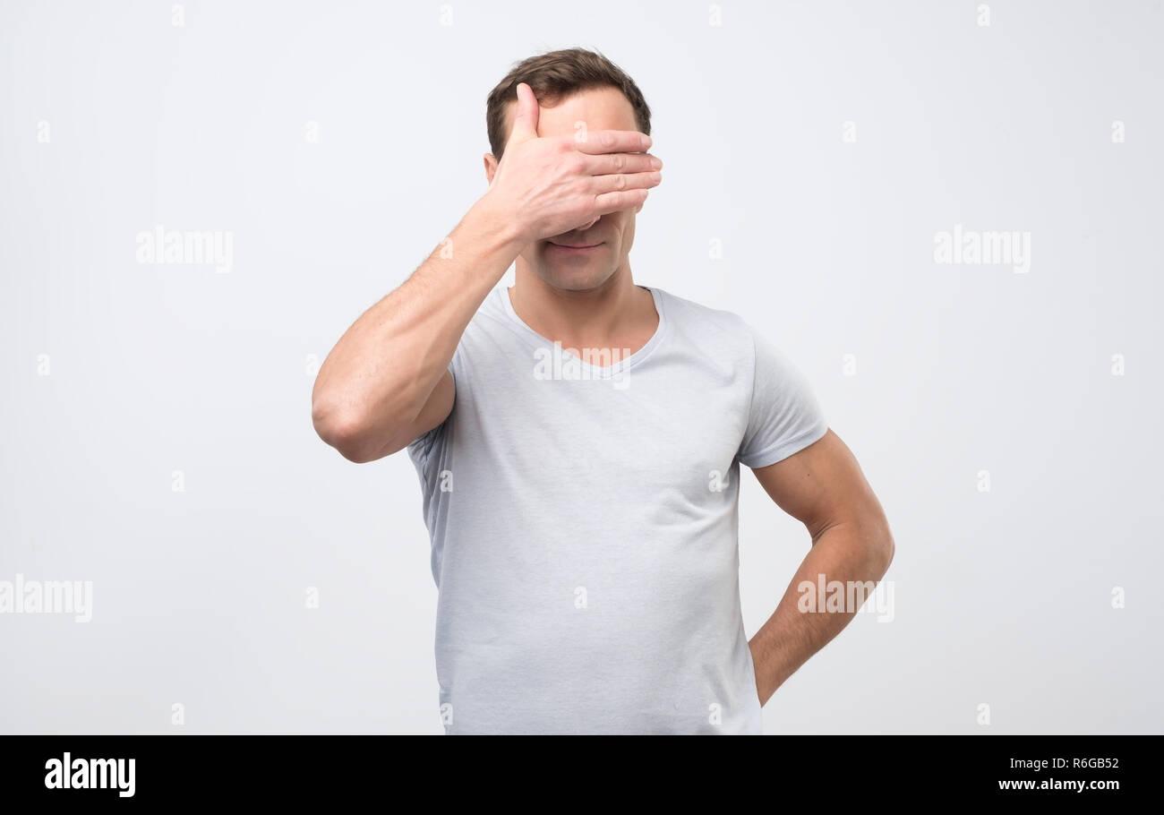 Nicht erkennbare Mann mit die Augen und fühlen sich schämen, sich gegen leere studio Wand Stockbild