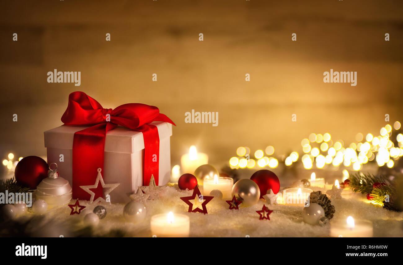 Weihnachten Szene mit einem weißen Geschenkbox, roten Bogen, Kerzen, Lichter, Kugeln und Schnee, mit braunen Kopie Raum Stockbild