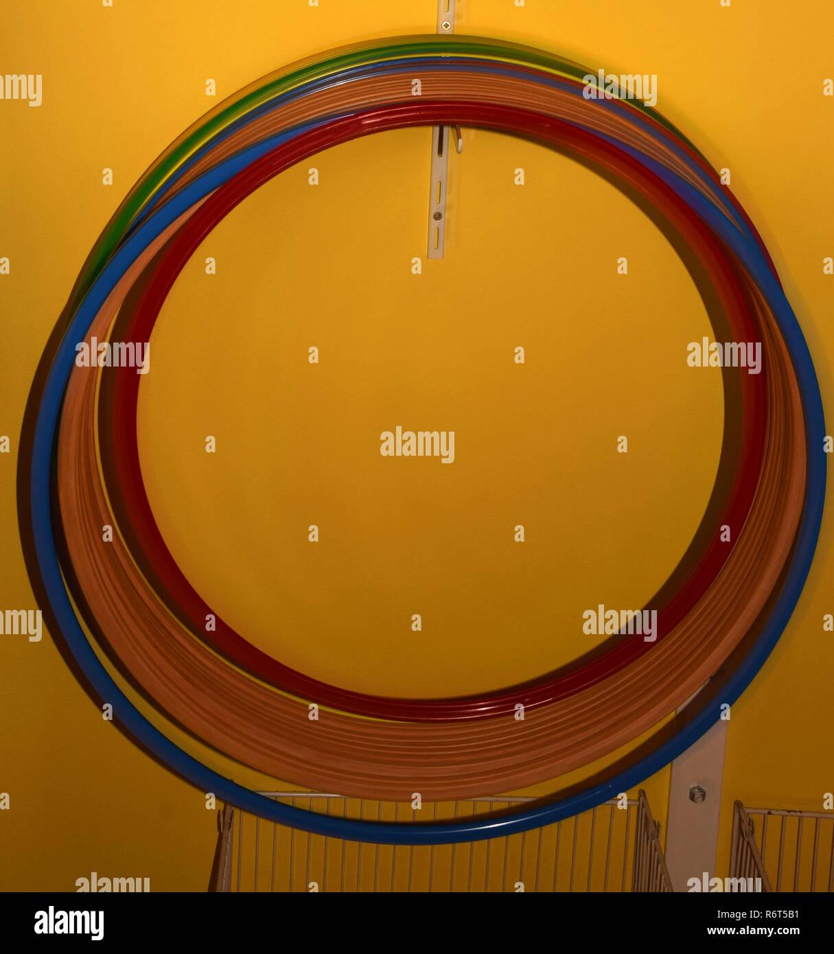 Hula Hoops ohne Menschen, Hula Hoops aus verschiedenen Materialien und Farben hängt an einem Haken vor gelbem Hintergrund Stockbild