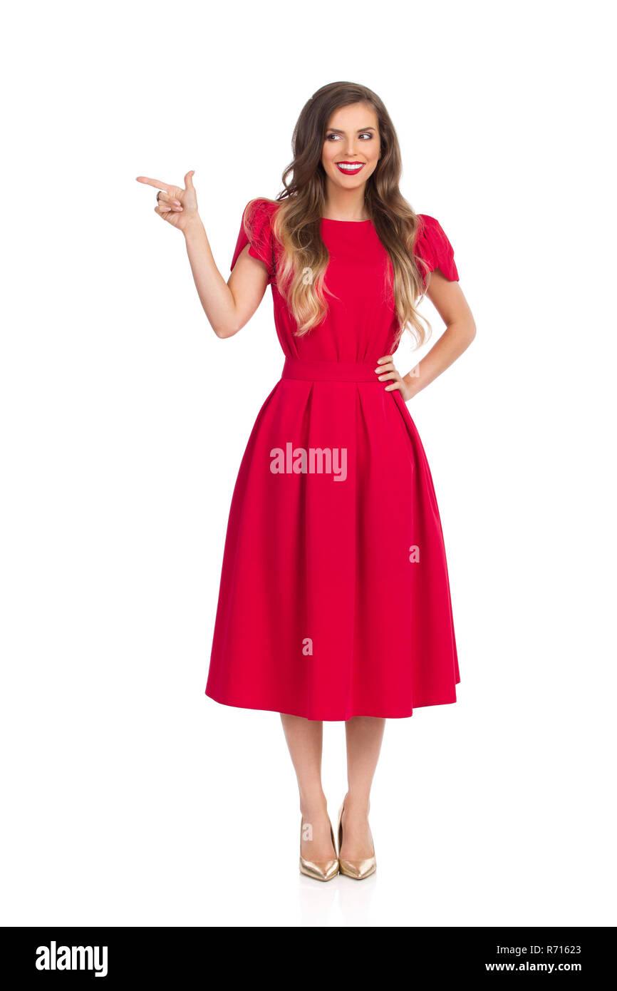 25c0d502739b6 Schöne junge Frau im roten Kleid und gold High Heels steht, und das ...