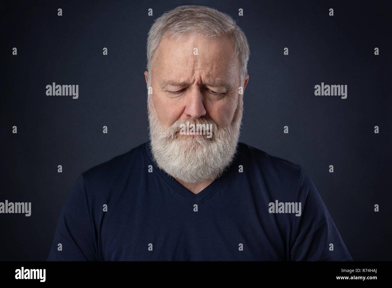 Älterer Mann mit grauen Bart nach unten schauen und Denken Stockbild