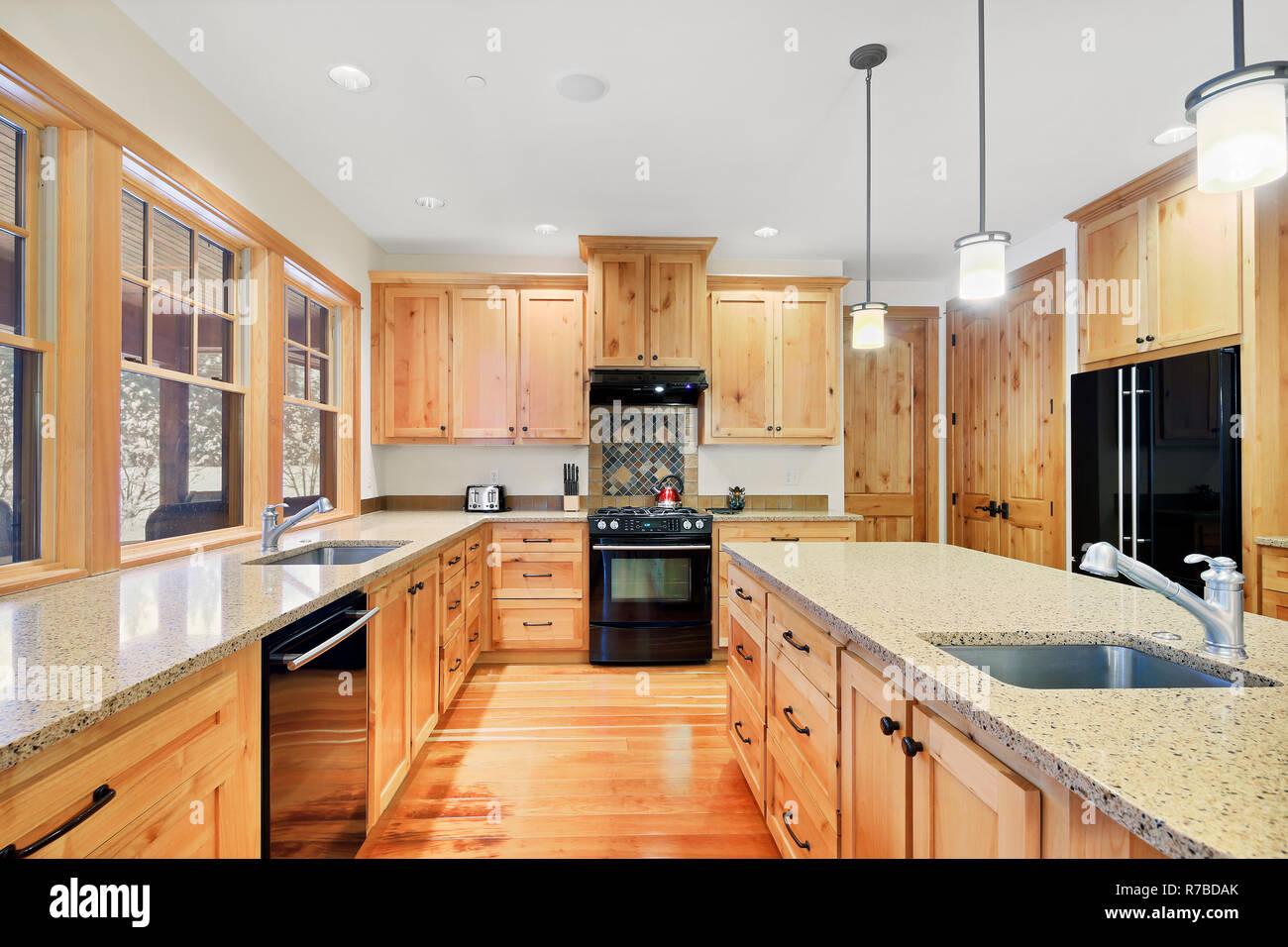 Schöne Küche Mit Hellem Holz Granit Und Schwarze Geräte Stockfoto