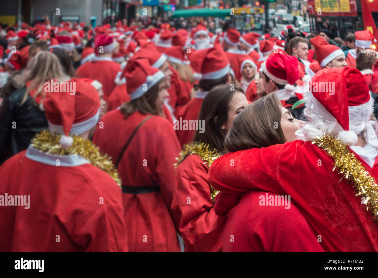 London, UK - Dezember 2018: Mann und Frau in santa Outfits küssen und umarmen einander, während die an einem themed SantaCon Ereignis gekleidet Stockfoto