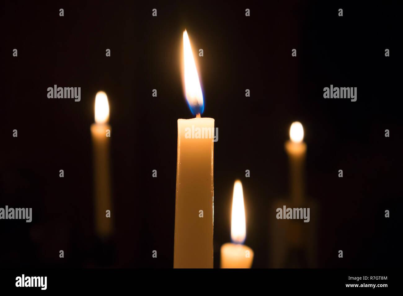 Eine Reihe von brennenden Kerzen geschmolzen mit unscharfen Gabeln der Flamme gegen den dunklen Hintergrund Stockbild