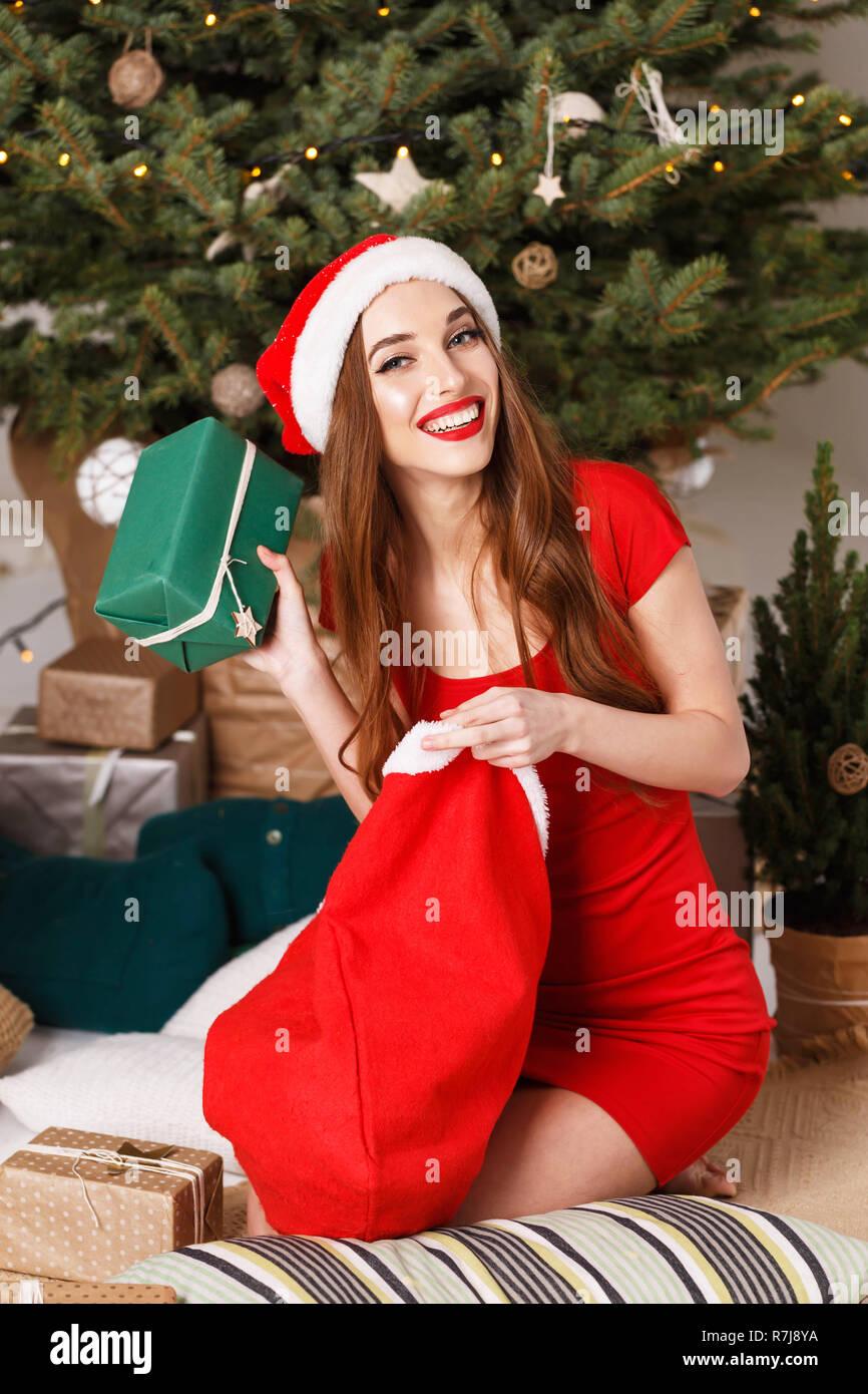 Geschenke Weihnachten Frau.Süße Weihnachten Frau In Santa Hat Und Red Sitzen Auf Dem Boden In