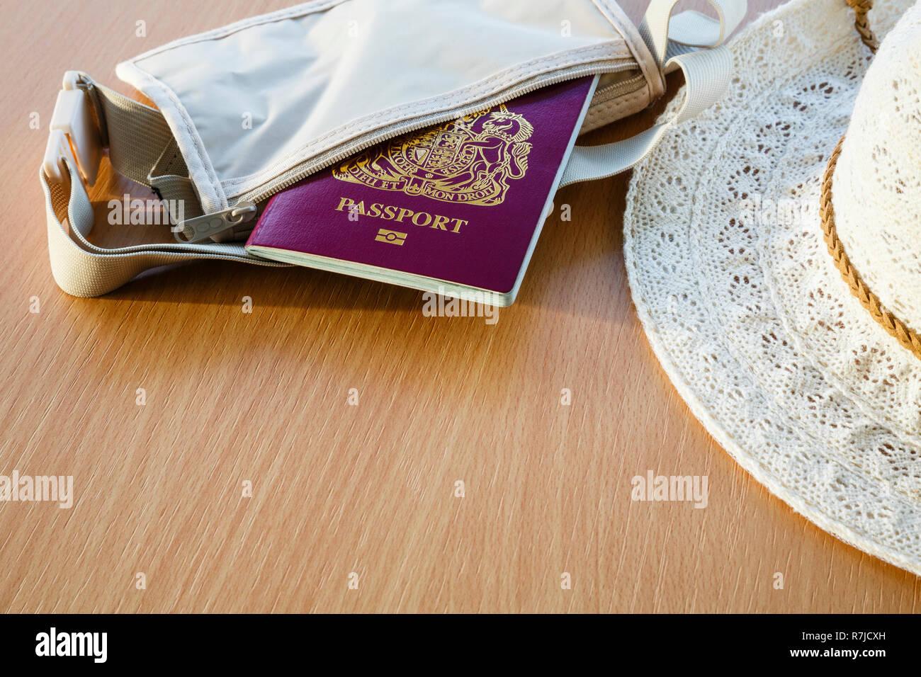 Reisen, für Reisen ins Ausland Britischen biometrischen Pass in einer Mappe mit Frauen Sonnenhut auf einem Tisch. England, Großbritannien, Großbritannien Stockbild