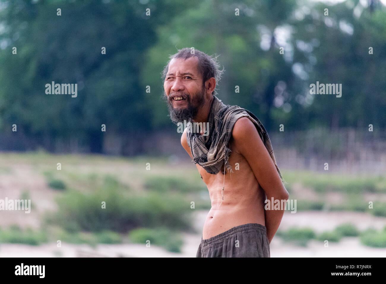 Don Daeng, Laos - 27. April 2018: Shirtless senior lokaler Mann gehen durch einen Strand in einer abgelegenen Insel des Mekong in Laos. Stockfoto