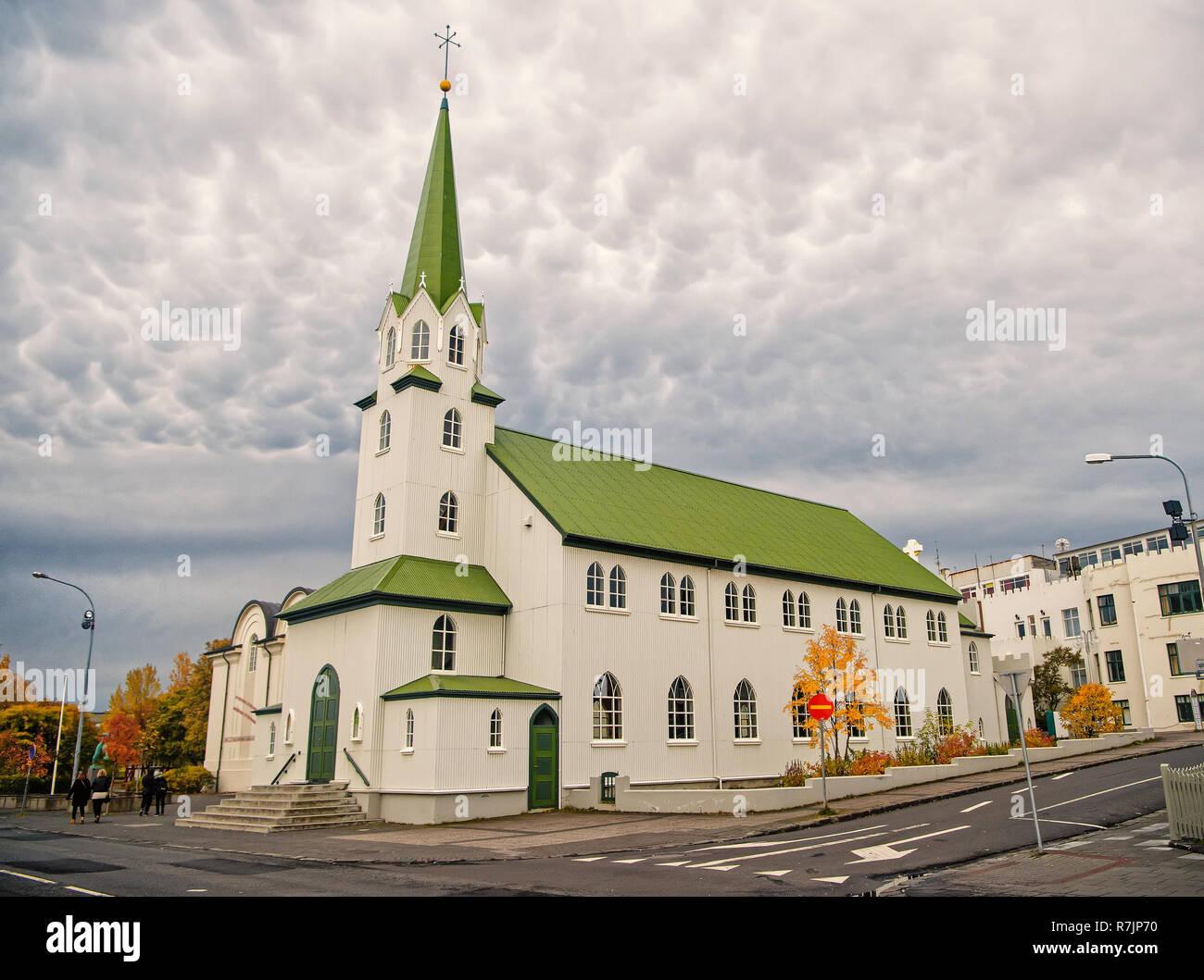 Kirche Gebäude mit weißen Wänden und grünen Dach auf bewölkten Himmel in Reykjavik, Island. Architektur, Sehenswürdigkeiten, Gottesdienst, Religion, Glauben Konzept Stockbild
