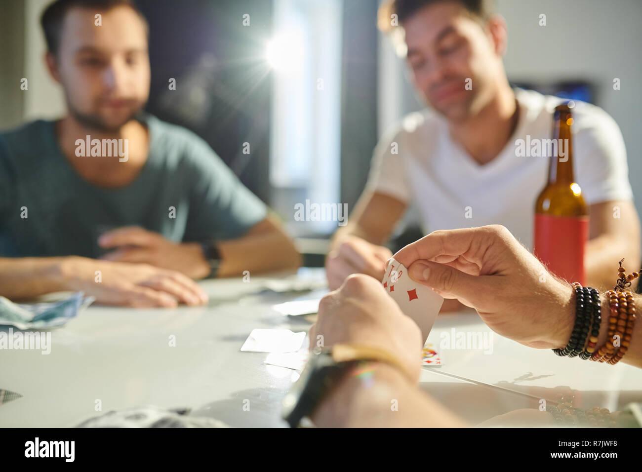 Nahaufnahme der männlichen Händen hält zwei Trümpfe beim Spielen in Karten mit seinen Freunden am Tisch Stockfoto