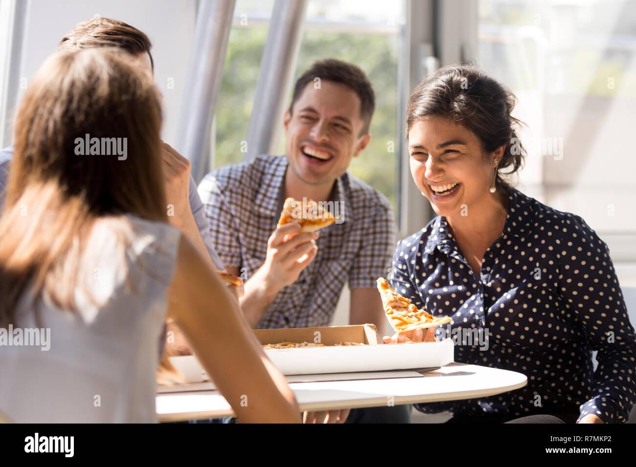Indische Frau Lachen Essen Pizza Mit Kollegen Im Buro Stockfoto