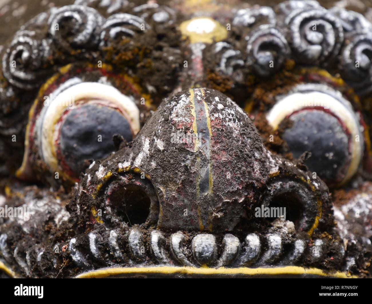 Nahaufnahme des Grotesken, furchtsames Gesicht der Statue des balinesischen Daemon, der mit weit aufgerissenen Augen und reißzähne im Pura Sangara Sea Temple in der Nähe von Sanur. Stockfoto