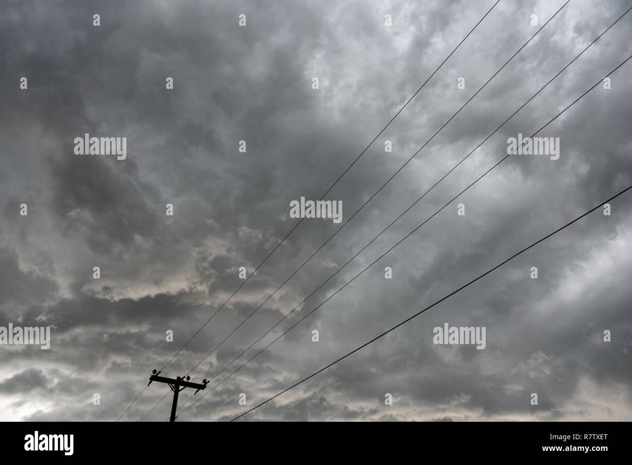 Elektrische Grid Infrastruktur, utility Pole und Overhead Stromleitungen gegen den blauen Himmel und Wolken in Wyoming/USA. Stockfoto