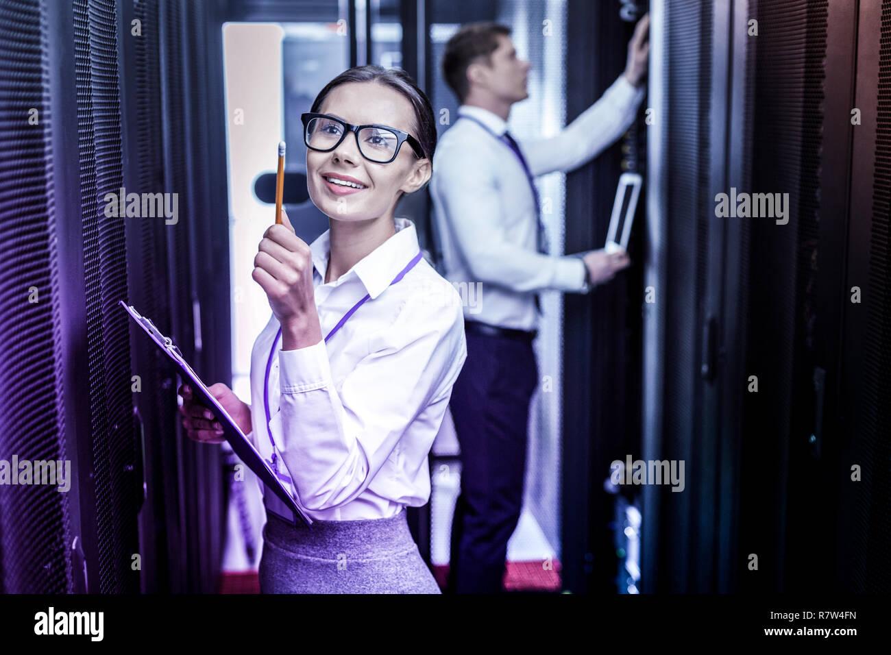 Freudige intelligente Frau zeigt mit einem Bleistift Stockbild