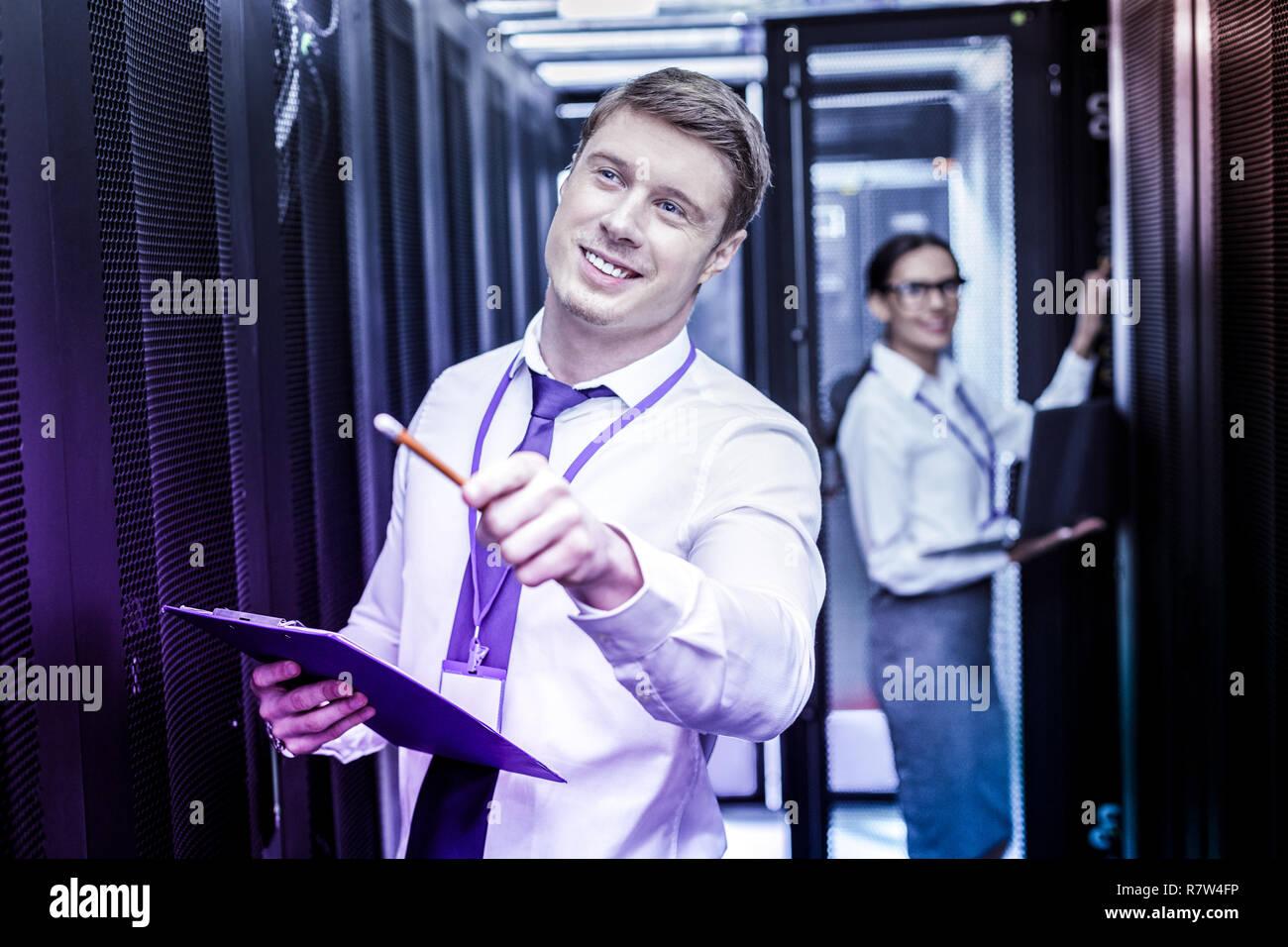 Netter Mann mit einem Bleistift in der Hand begeistert Stockbild