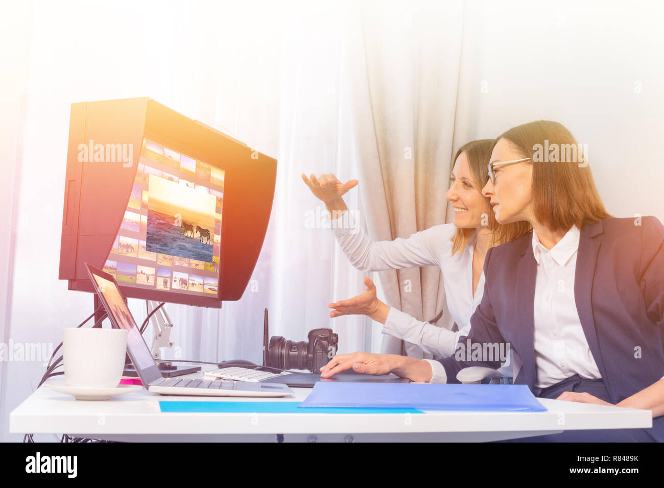 Porträt der Fotografin und Client arbeiten mit Computer, mit Fotosoftware im Büro Stockbild