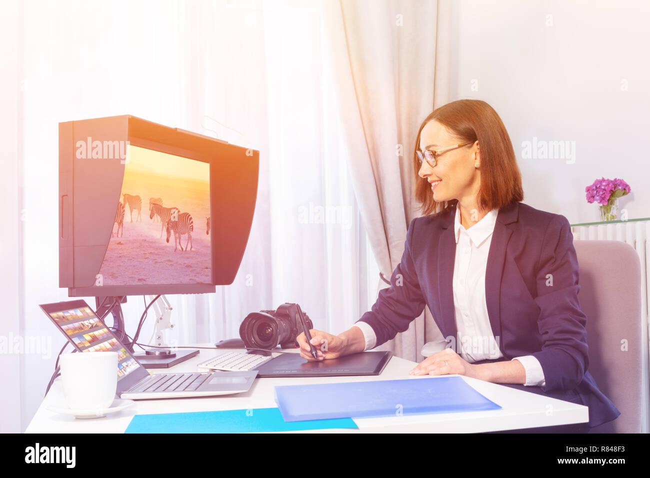 Portrait von lächelnden Geschäftsfrau mit Bildern arbeiten, über digitale Zeichnung Monitor im Büro Stockbild