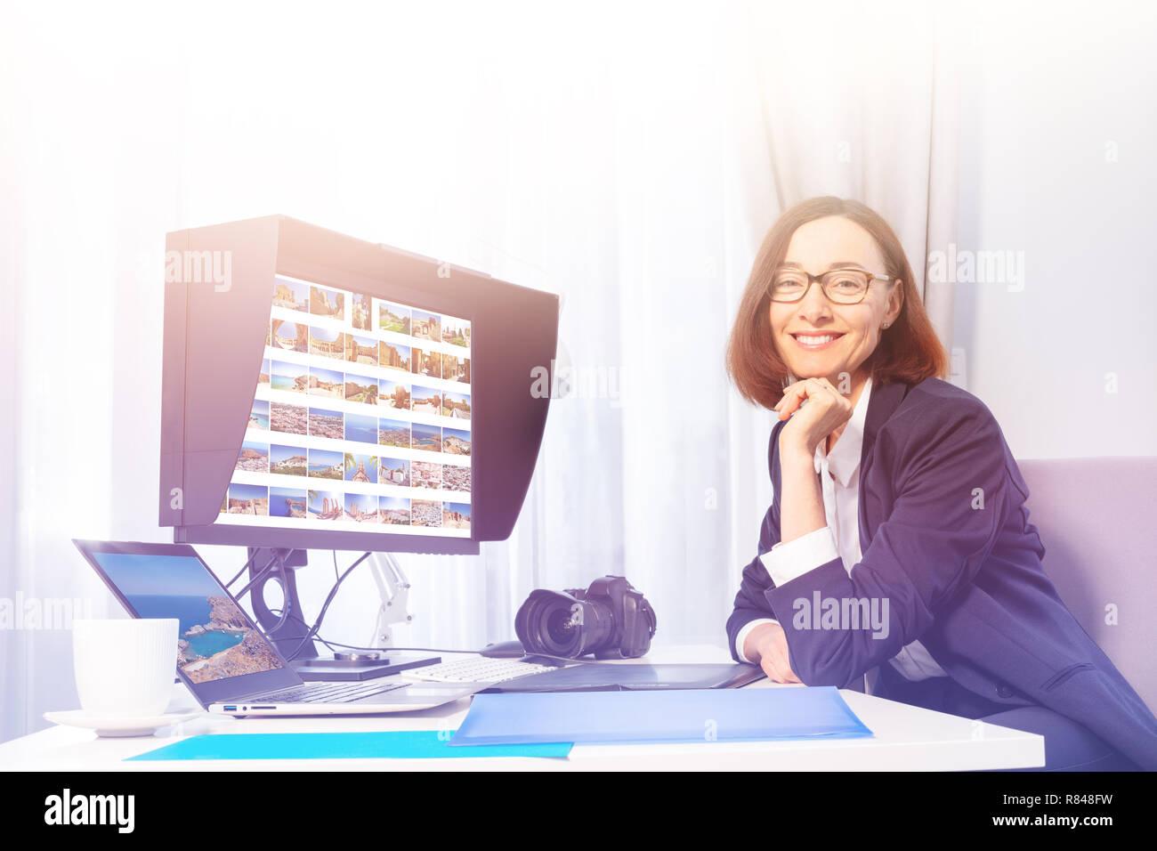 Porträt der Fotografin arbeiten mit Image editor, sitzen vor dem Computer Monitor, lächelnd und suchen Kamera Stockbild