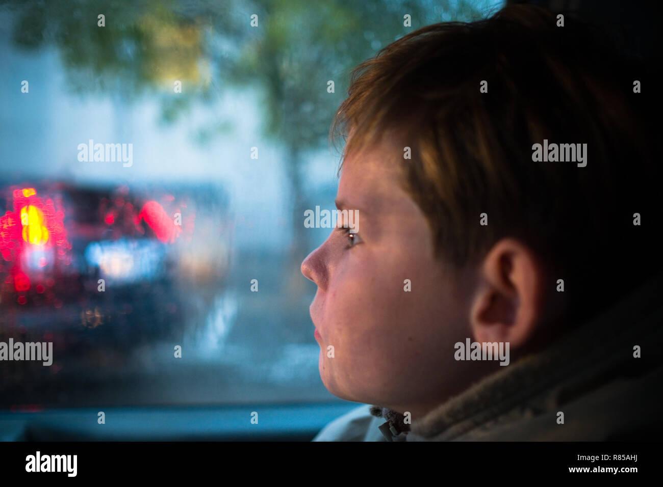 Nahaufnahme Seite Profil des 11 Jahre alten Jungen im Auto auf dem Weg zur Schule Blick aus dem Fenster an einem vorbeifahrenden Auto im Regen Stockbild