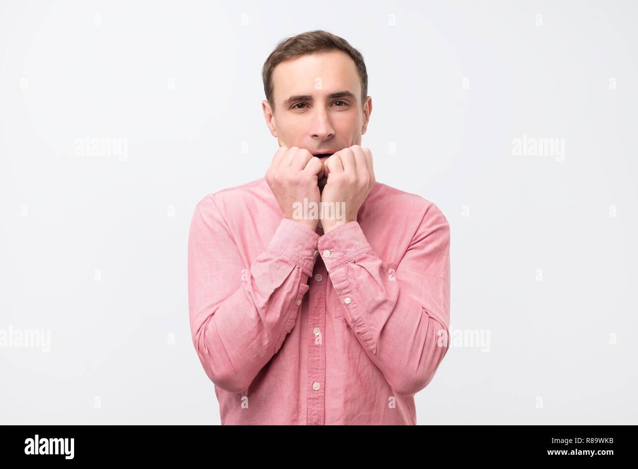 Junger Mann hat Angst, die Finger in der Nähe von Mund Stockbild