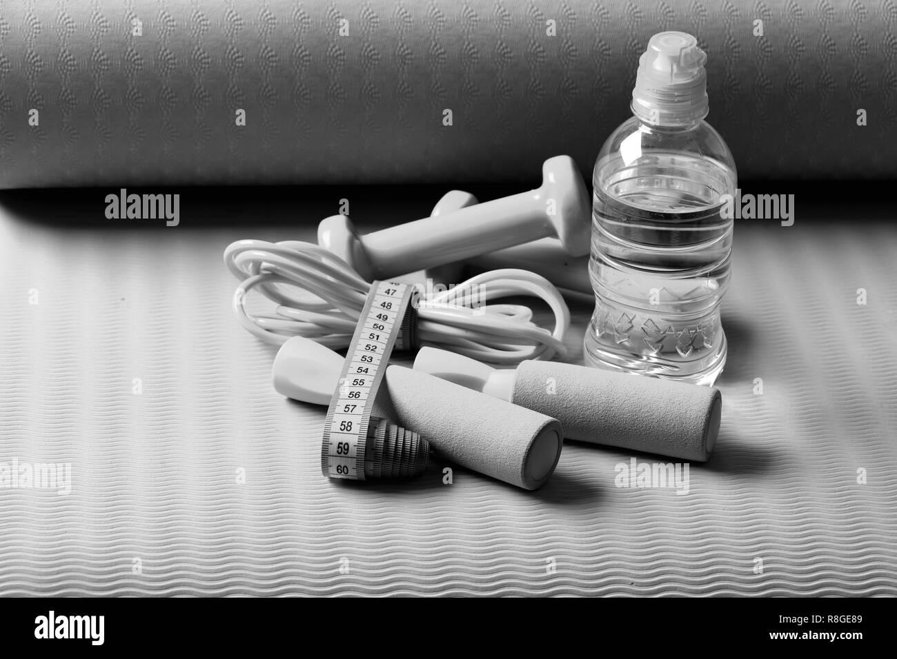 Springseil, Wasserflasche und cyan Kurzhanteln mit Maßband auf Grün und Lila Hintergrund gebunden. Mit Seil springen und Langhanteln auf Yoga Matte Band. Sport und Gesundheit. Fitness- und Erfrischung Konzept Stockbild