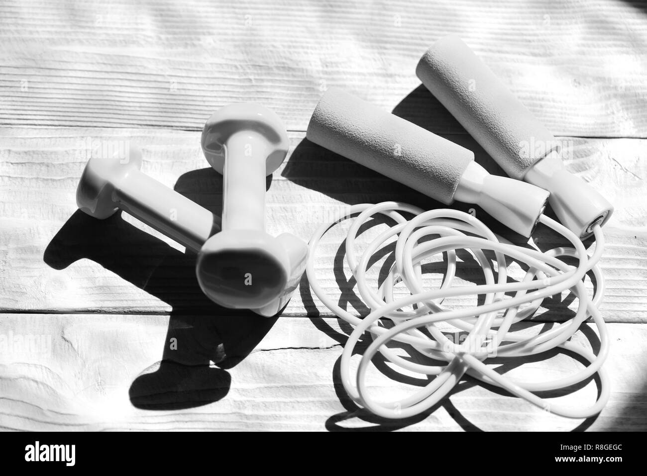 Hanteln und unordentliche Springseil platziert quer. Gesunde Form und Sport Konzept. Gestaltung und Fitnessgeräte. Hanteln und Seil in Cyan blaue Farbe springen Sie auf hellen Hintergrund Stockbild