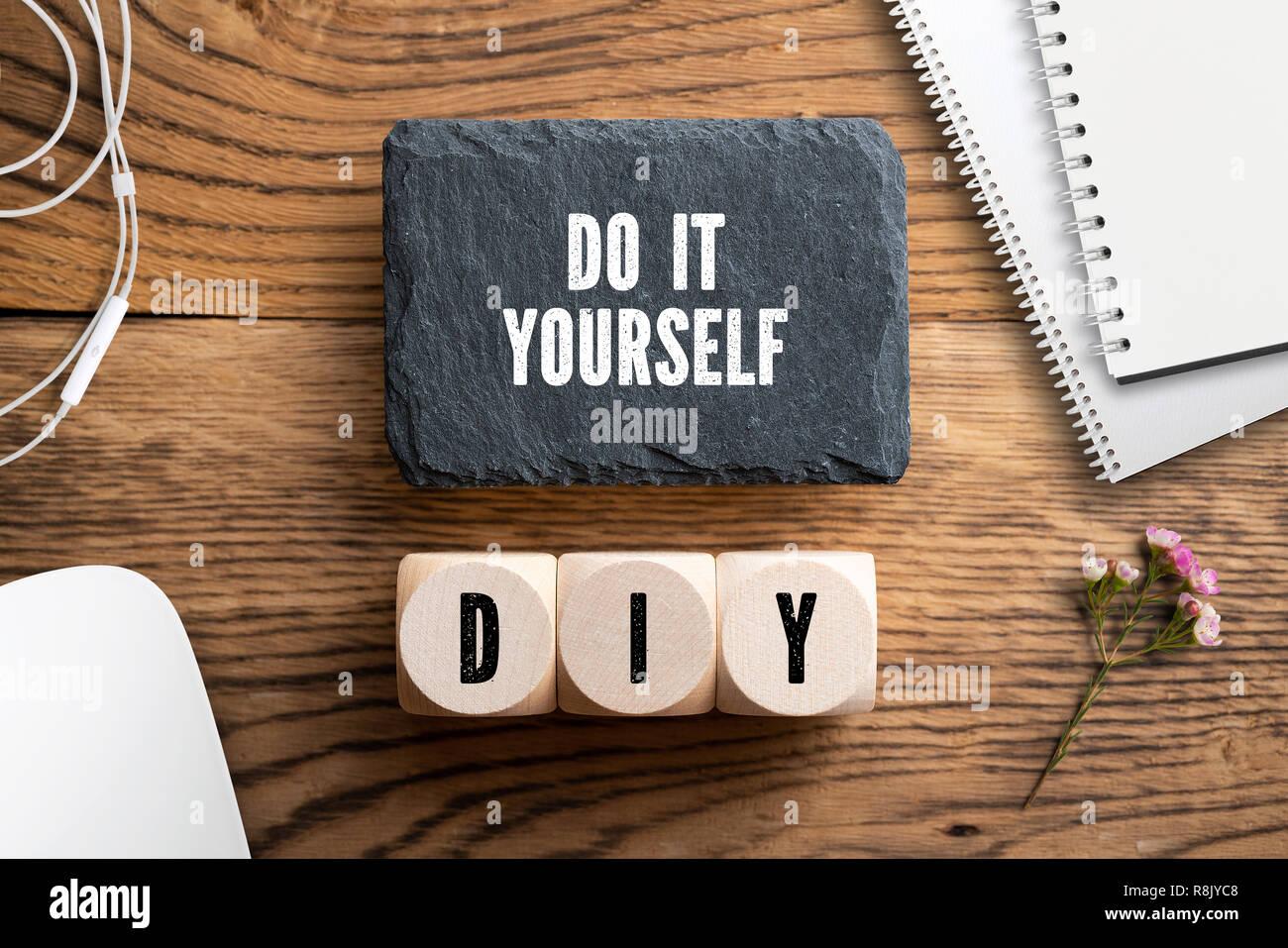 Meldung 'Do it yourself' und Würfel mit akronym DIY auf hölzernen Hintergrund Stockbild