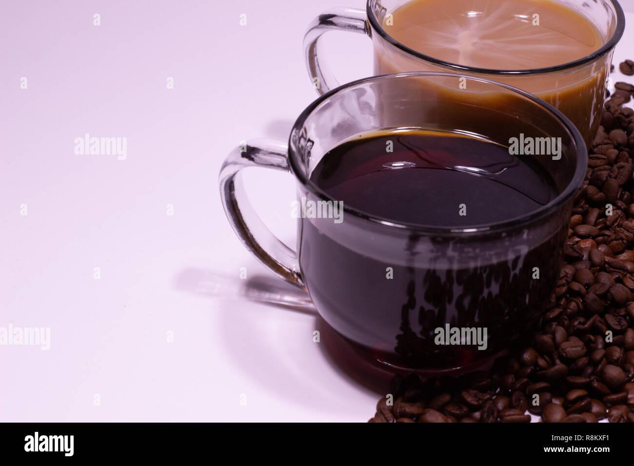 Zwei Glas Kaffeetassen auf einem weißen Tisch neben Kaffeebohnen Stockfoto
