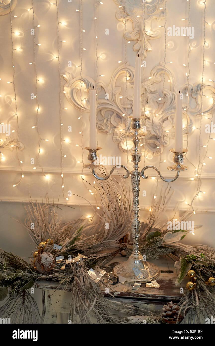 Drei - Horn Kerzenhalter, Girlande. Weiß und Silber Dekor. Das neue Jahr Atmosphäre. Weihnachten Dekoration zu Hause. Stockbild