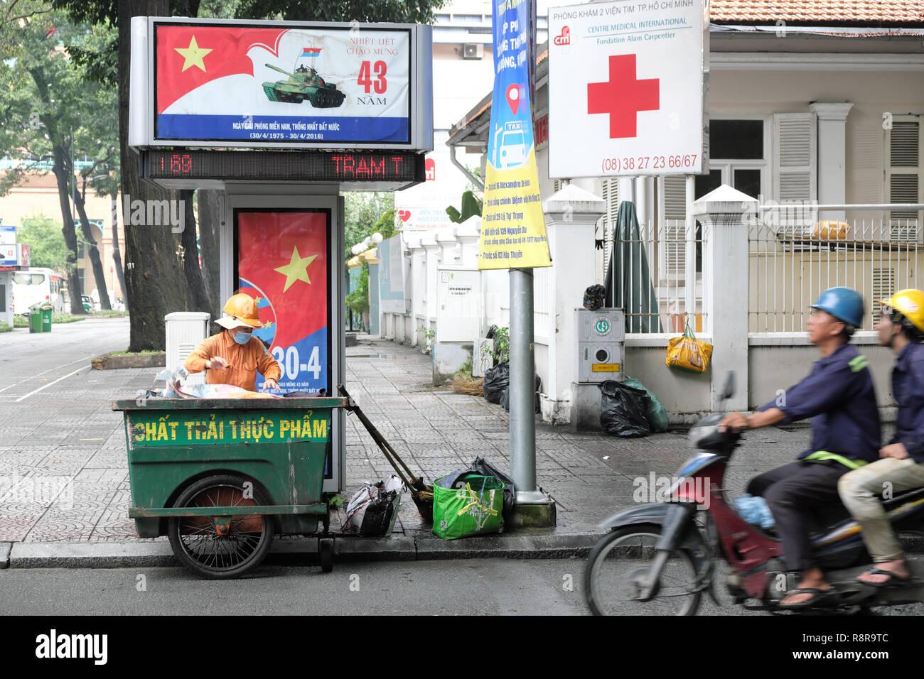 Ho Chi Minh City, Vietnam - Street Sweeper Reinigung Straßen in der Nähe der Kommunistischen Partei Plakate feiert 43 Jahre seit die Stadt wurde 1975 befreit Stockbild