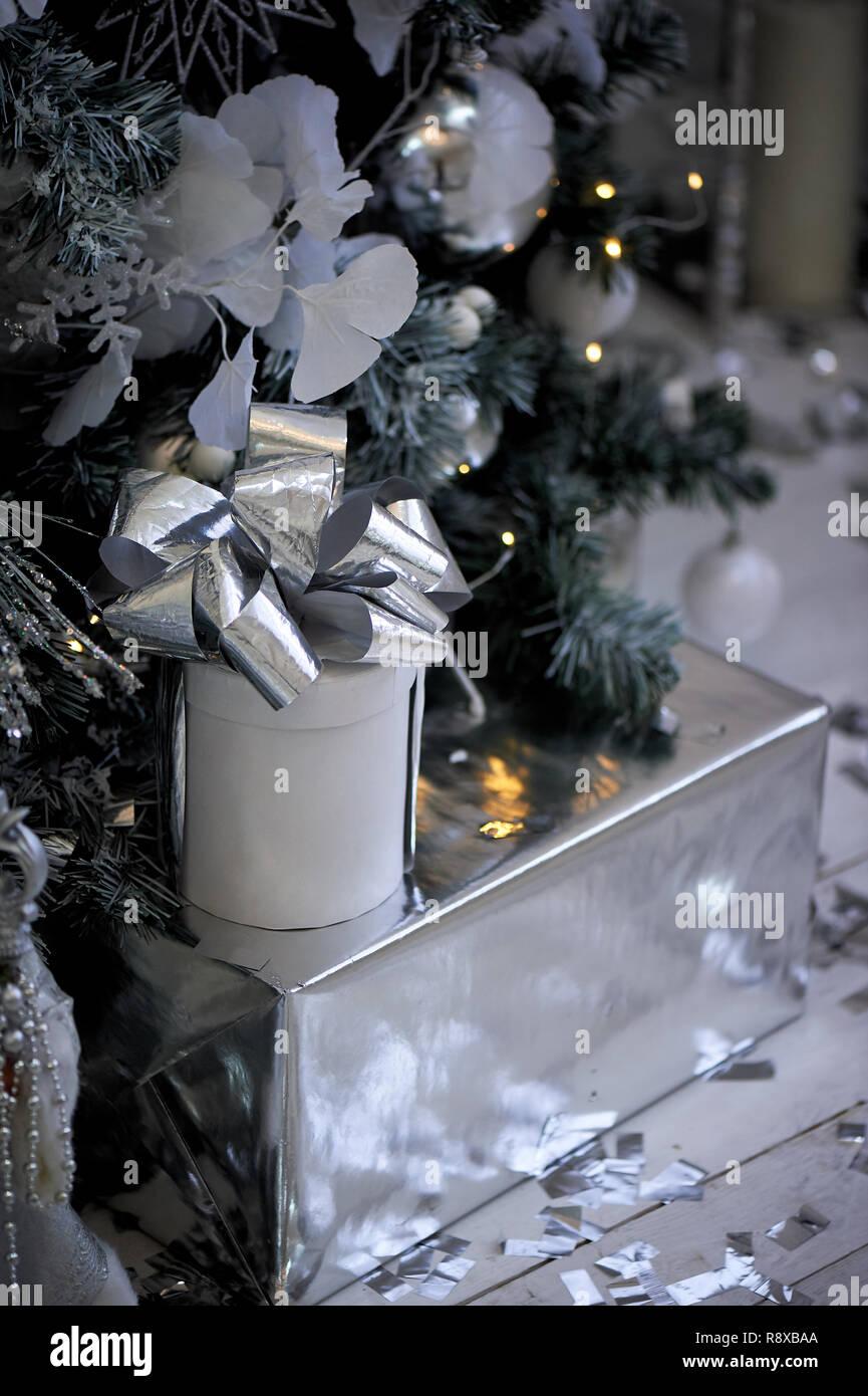 Geschenk Silber Verpackung Papier unter dem Weihnachtsbaum im neuen Jahr. Stockbild