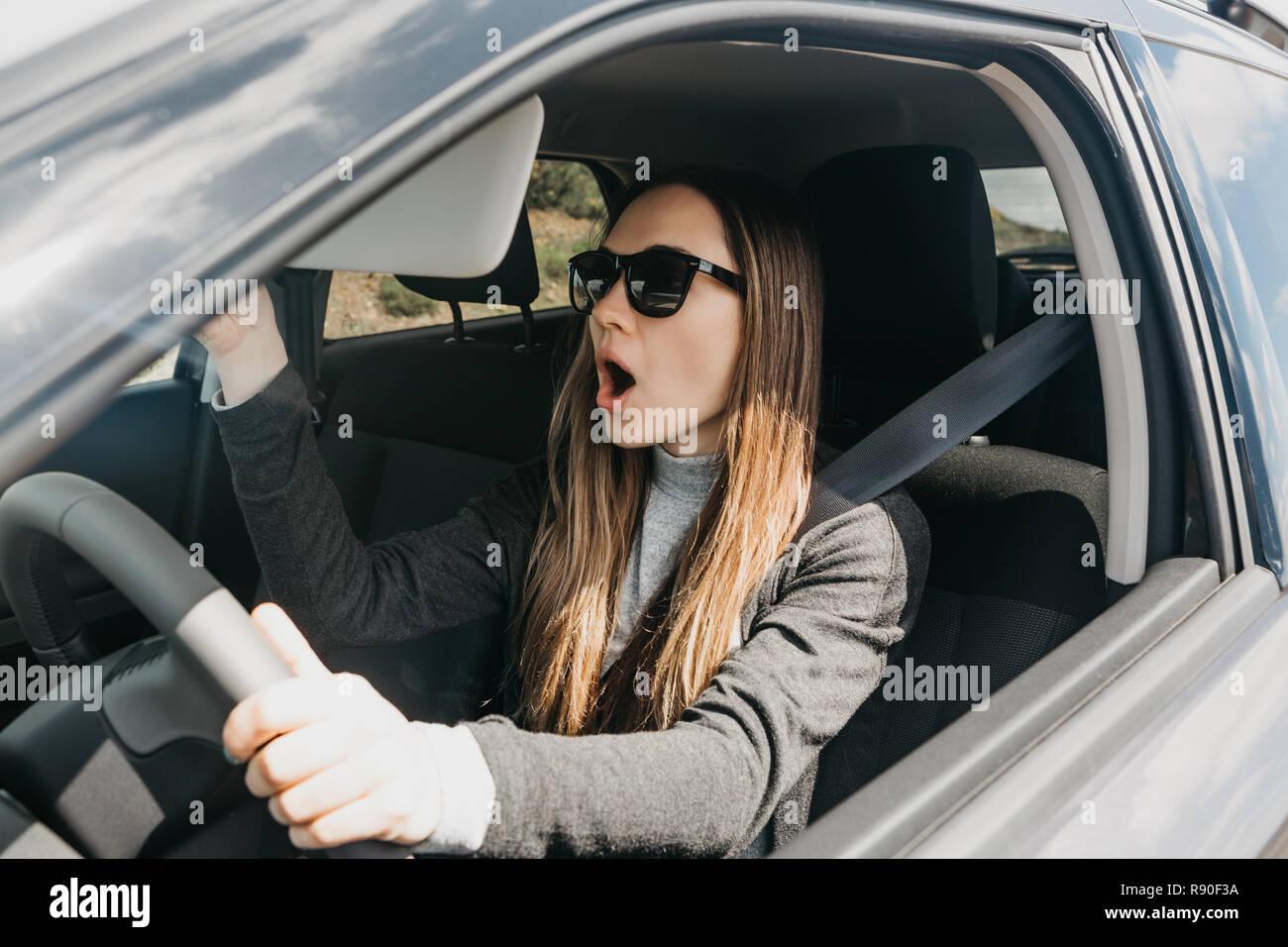 Das Mädchen oder der Fahrer im Auto überrascht oder erschreckt oder etwas passiert ist und sie zeigt Gefühle. Auto fahren. Stockbild