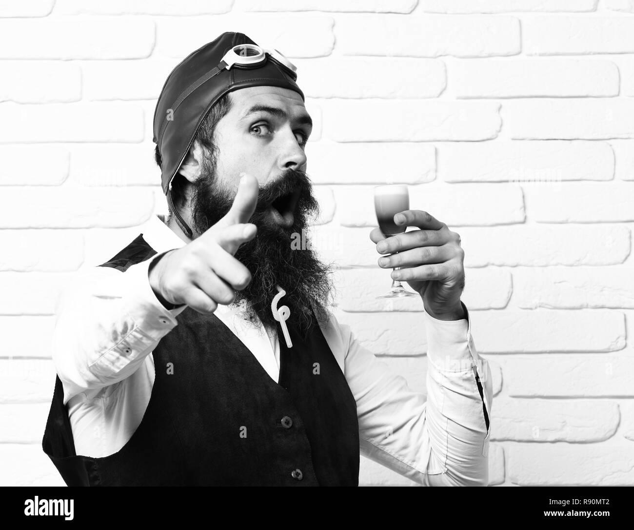 Schöne bärtige aviator Mann mit langem Bart und Schnurrbart auf überrascht Gesicht holding Glas alkoholische Schuß in Vintage Leder weste mit Hut und Brille auf der weißen Wand Hintergrund. Stockfoto