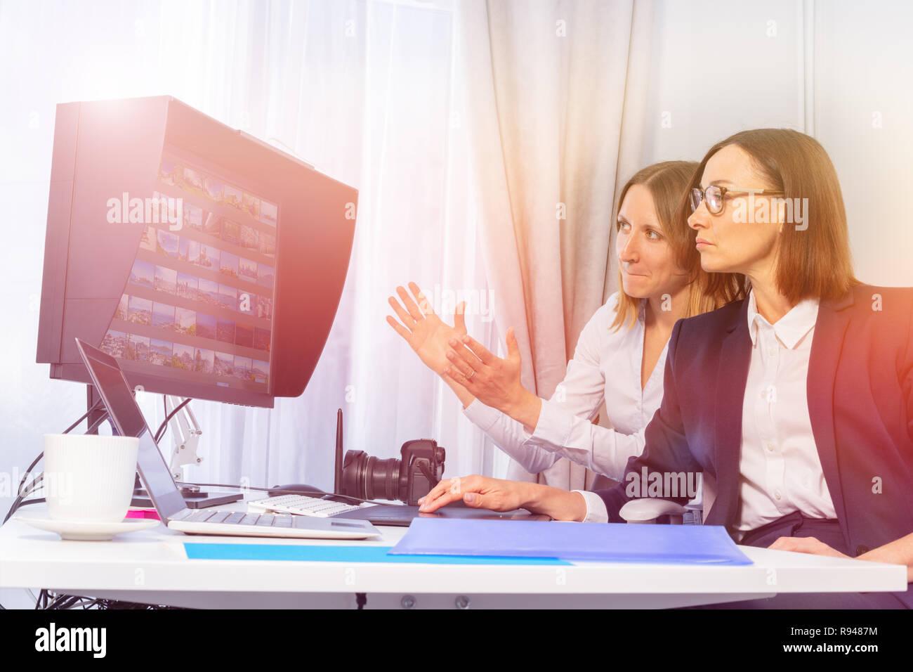 Porträt der Fotografin und Client vor dem Monitor sitzen, diskutieren Portfolio Bilder Stockbild