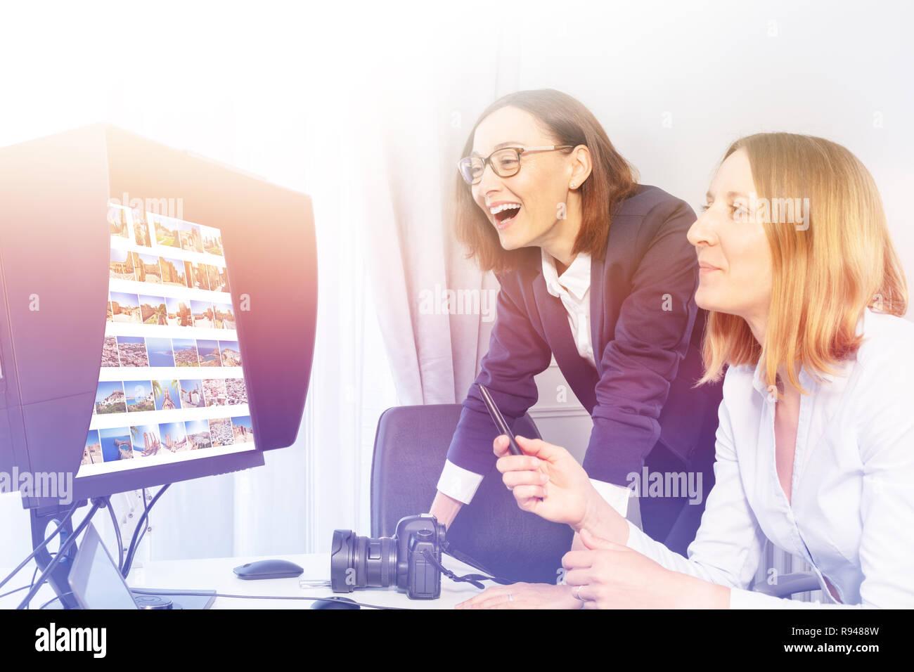 Porträt der Fotografin und Client am Computer Schreibtisch sitzen, diskutieren Portfolio Bilder im Büro Stockbild
