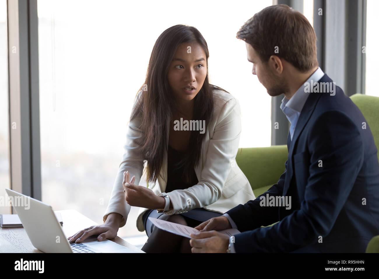 Asiatische kaukasischen Kollegen sitzen auf der Couch diskutieren lösen Stockbild