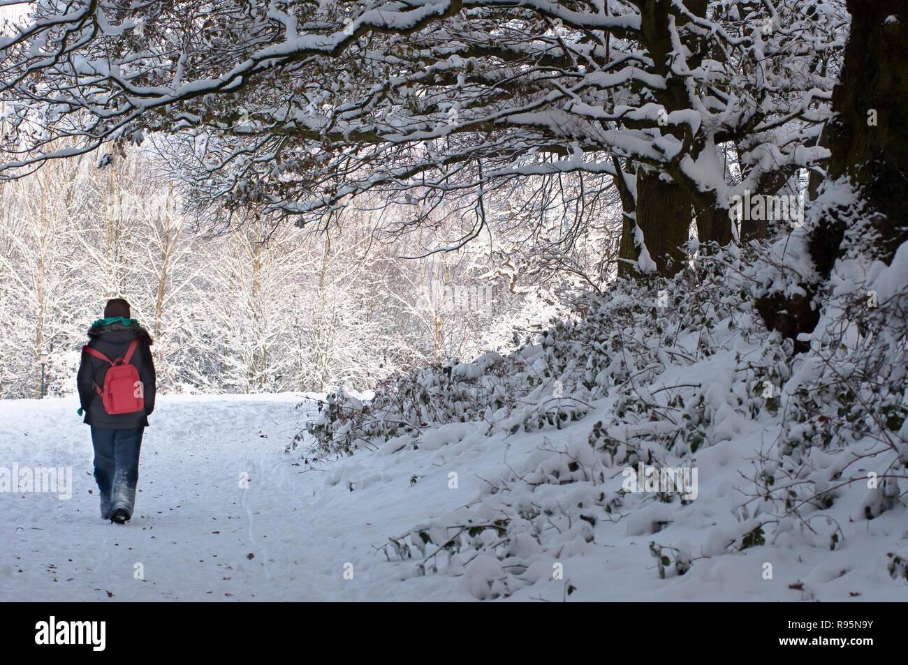 Frau auf einem schneebedeckten Weg in Redditch, Worcestershire. Großbritannien Stockfoto