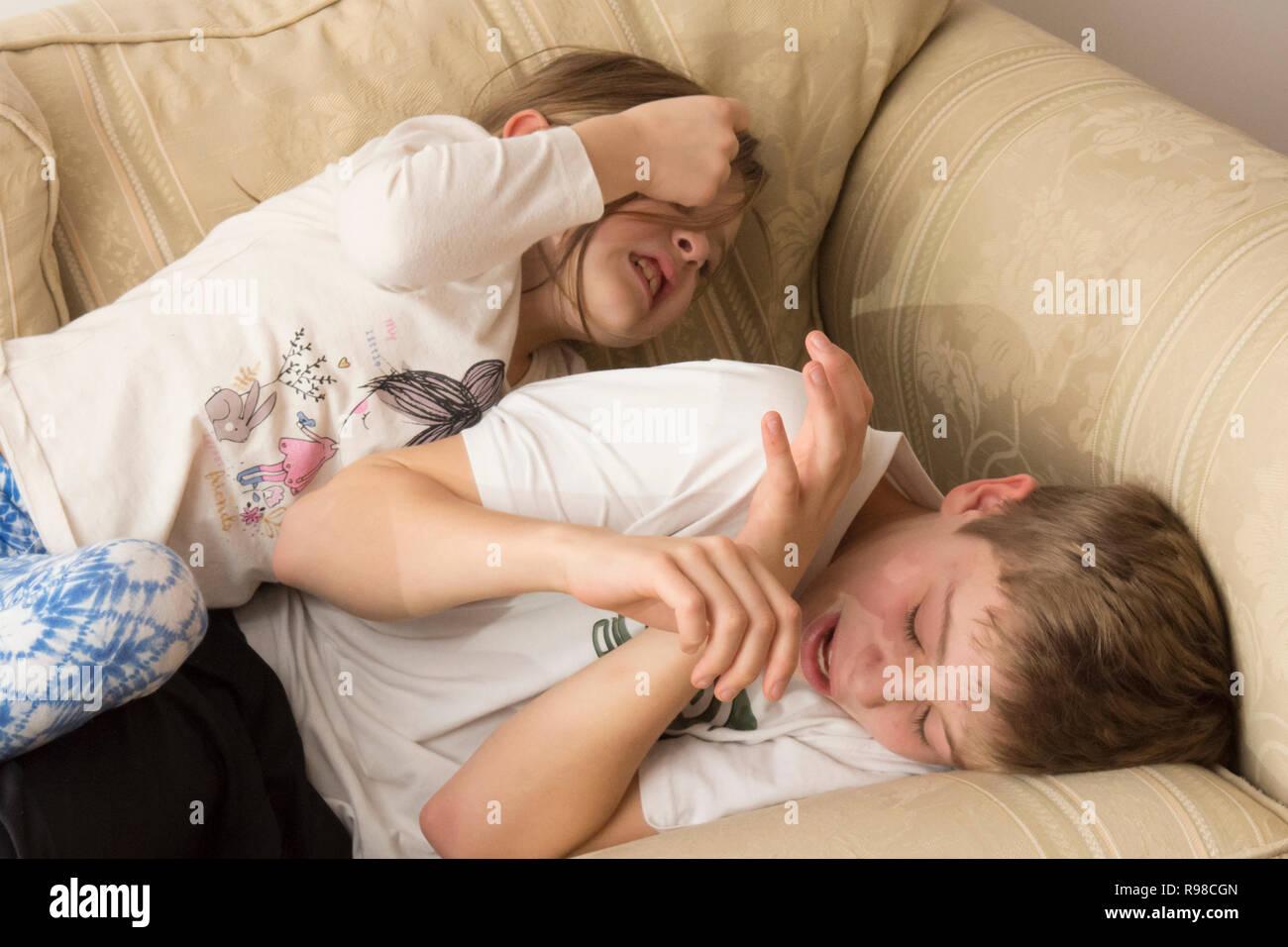 Kinder, Junge und Mädchen, Bruder und Schwester, Geschwister, spielen, kämpfen, kämpfen, Ringen, laut, gewalttätig, auf dem Sofa, zwölf Jahre alt, sechs Jahre alt. Stockfoto
