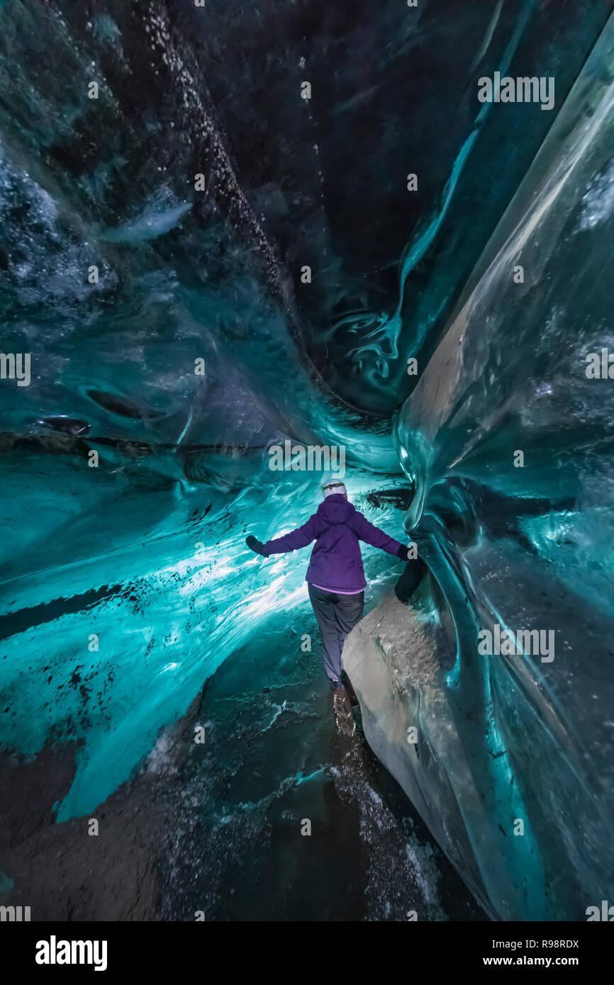 Karen Rentz in einer Eishöhle innerhalb einer Nocke der Gletscher Myrdalsjökull, die auf Katla Vulkan sitzt, im Winter in Island Stockfoto