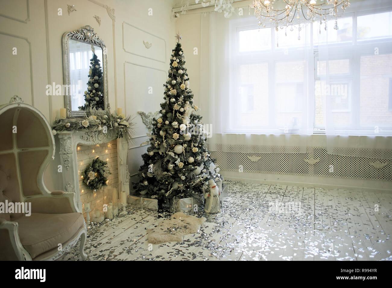 Massive alten Stuhl mit Licht Stoffbezüge und hohen Rücken geschlossen. Das neue Jahr Atmosphäre. Palace Interieur mit Weihnachtsbaum Stockbild