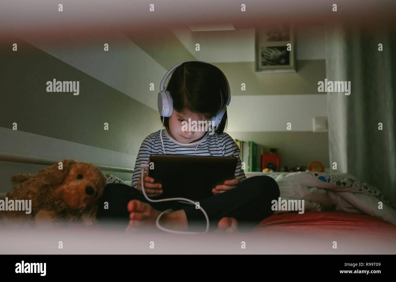 Kleines Mädchen mit Kopfhörer auf dem Tablett, auf dem Bett zu sitzen in der Nacht Stockbild