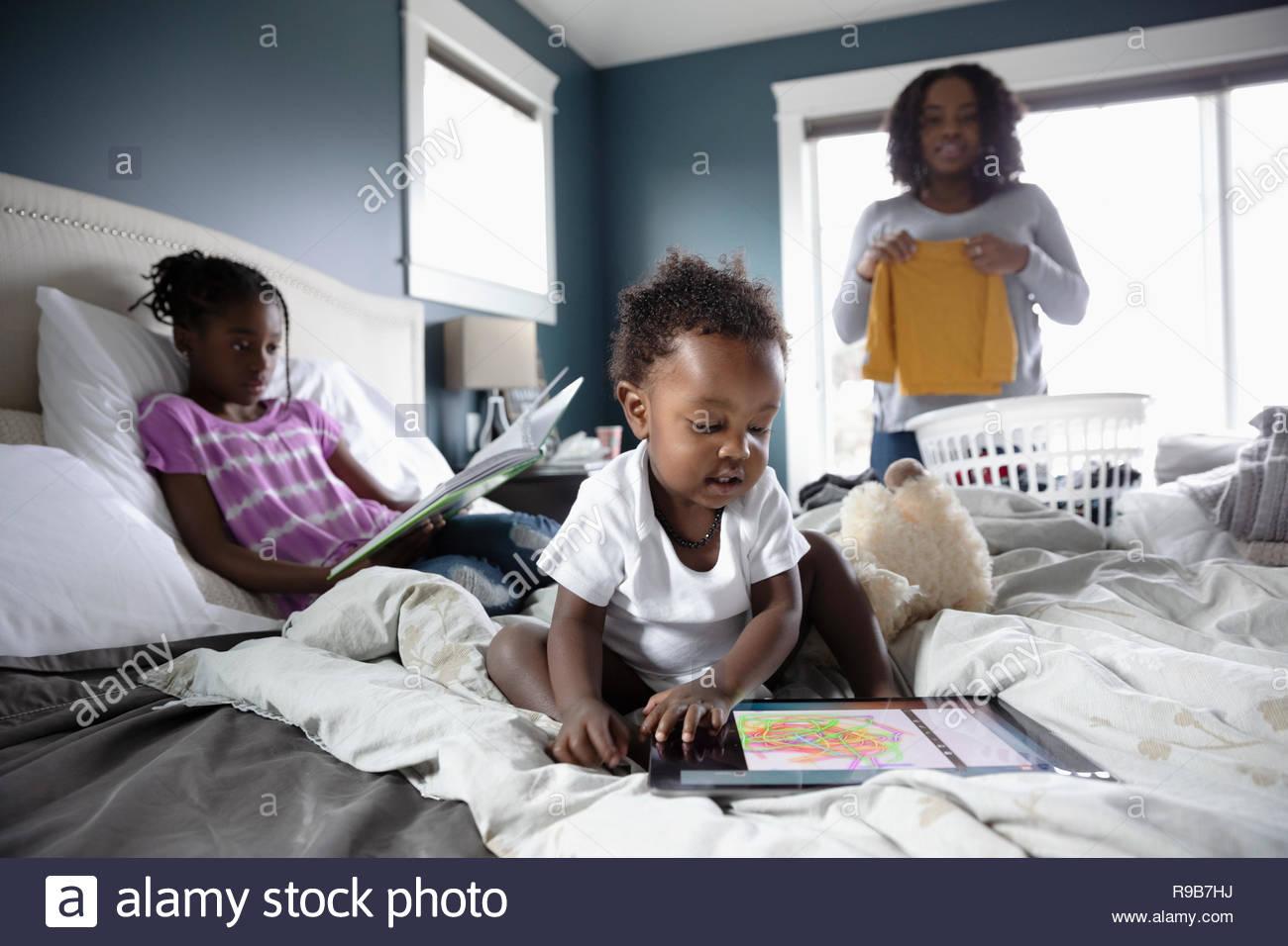 Mutter falten Wäsche während die Kinder Lesen und Spielen auf dem Bett Stockbild