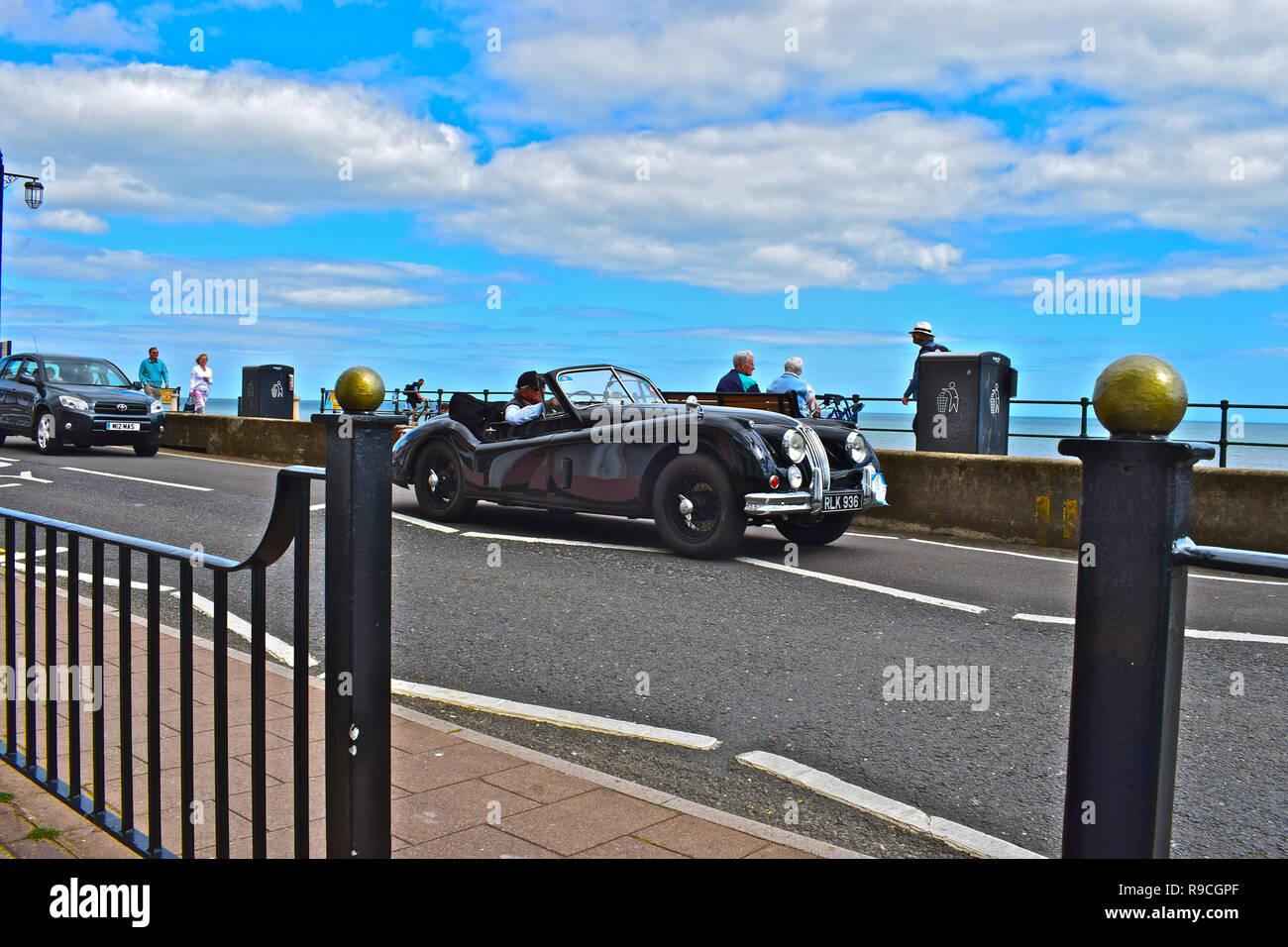 Ein klassischer Jaguar XK 120 Sport Auto fährt entlang der Esplanade in Sidmouth, während die Teilnahme an der Runde Großbritannien Coastal Drive 12-29. Juni 2017. Stockbild