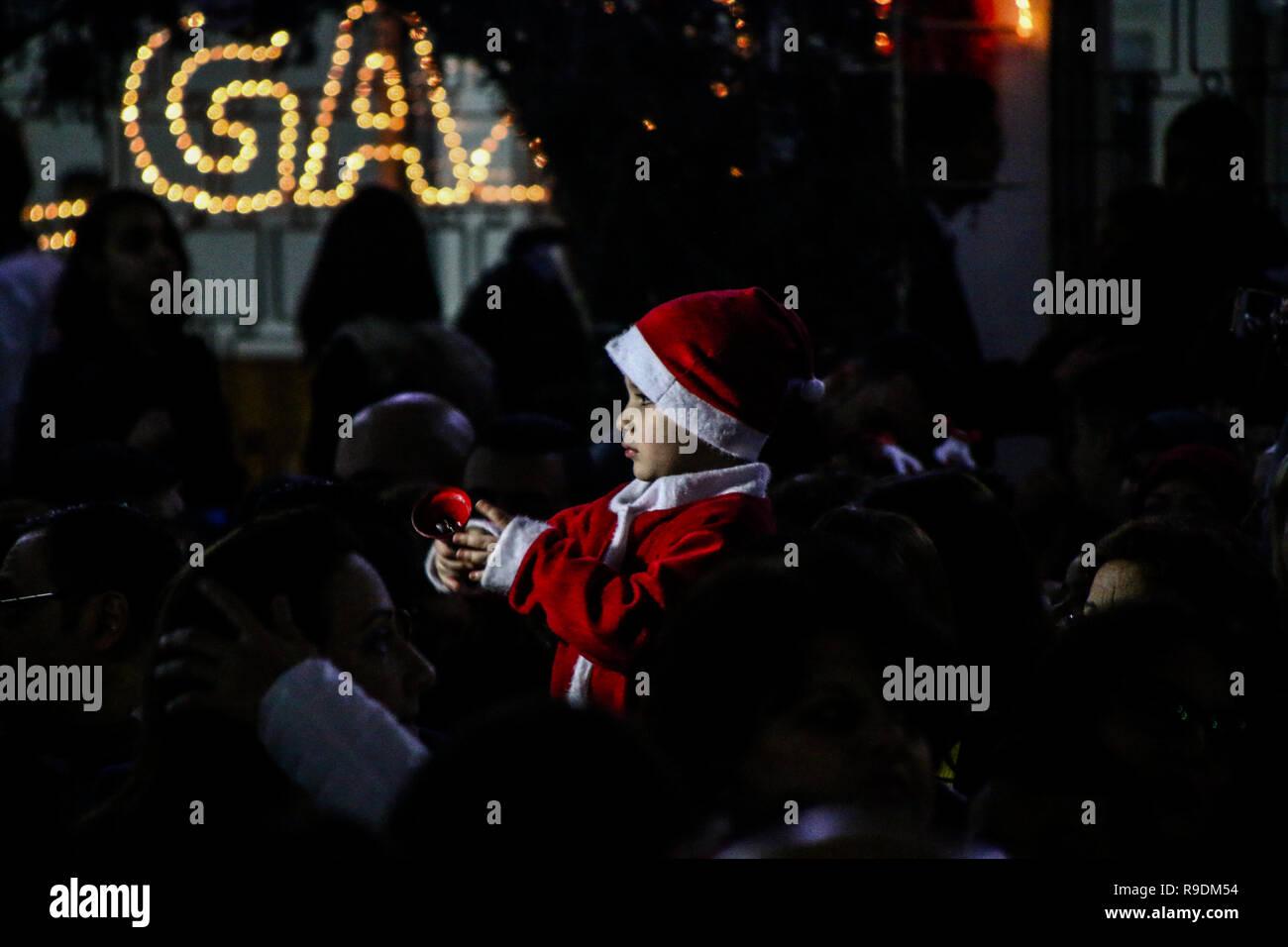 Gaza, Palästina. 22. Dez 2018. Das YMCA im Gazastreifen den Weihnachtsbaum Zeremonie in seinen Platz in Gaza Stadt organisieren am Abend des 22. Dezember 2018. Eine palästinensische Folklore tanzen und den Segen eines griechisch-orthodoxen Patriarchen begleitet die Zeremonie in der bis zum Heiligabend. Christliche und muslimische Palästinenser converged auf dem Platz in Gaza zu feiern und den Dekorationen und andere Traditionen der Jahreszeit, wie Fotos der Kinder mit Santa Claus und Nächstenliebe Sammlungen für die Bedürftigsten zu genießen. Credit: ZUMA Press, Inc./Alamy leben Nachrichten Stockfoto