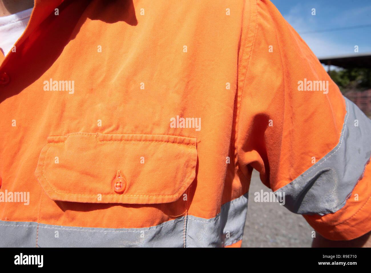 In der Nähe der linken Schulter vor Brust Tasche auf einer hohen Sichtbarkeit (Hi Vis) orange Arbeit Shirt ohne Beschriftung Stockfoto